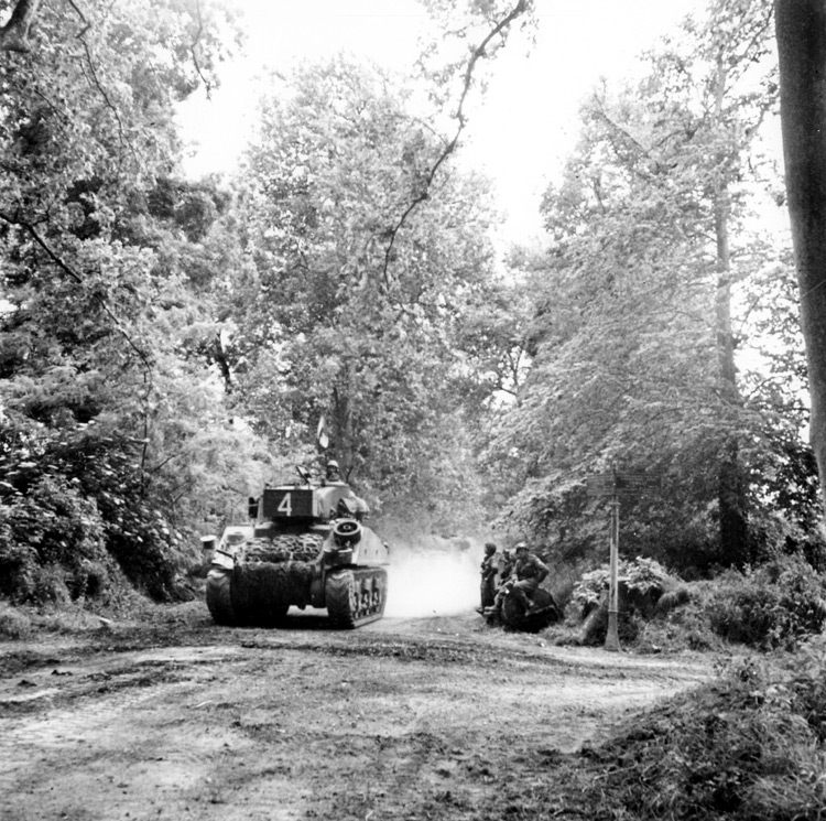 A Sherman medium tank, French tri-color hung from its aerial, leads a column. (National Archives of Canada PA 132801)